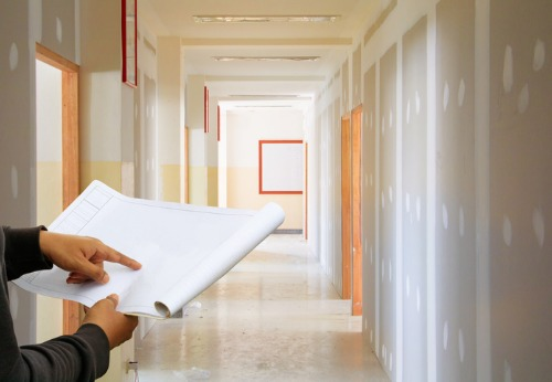 A builder looking at blueprints for Interior Contracting in Central Illinois for an office hallway